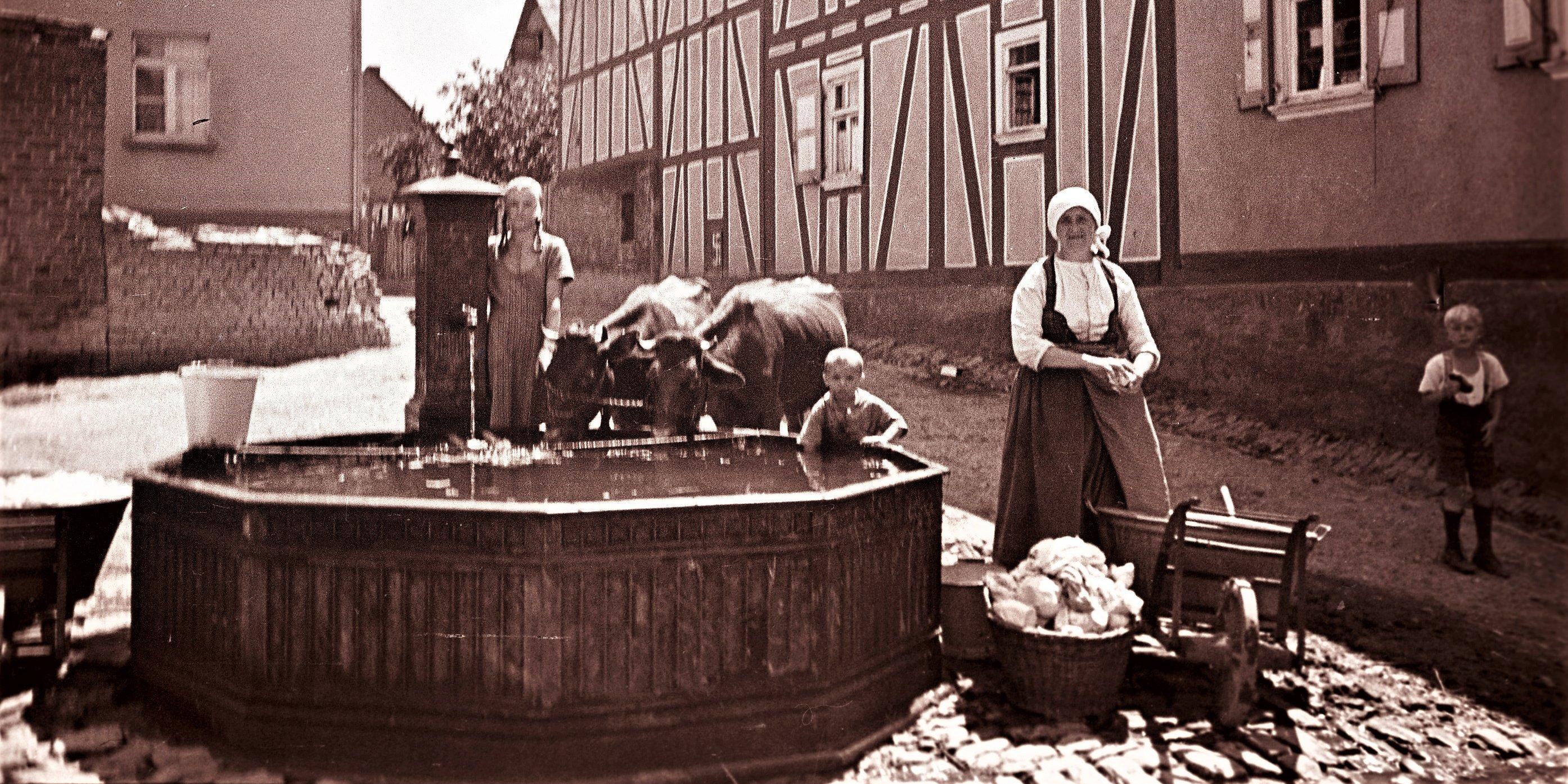 Frau und drei Kinder mit Rindern am Dorfbrunnen