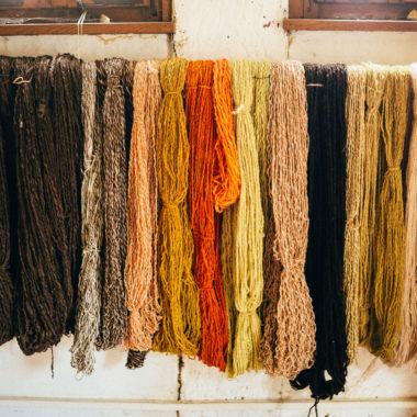 In der Wollwerkstatt sind die eingefärbten Wollstränge in einer Reighe auf einem Holzstab aufgehängt.